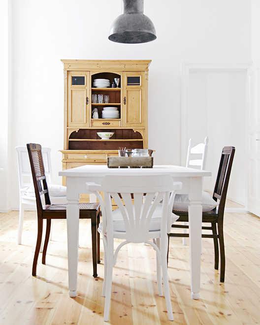 Esszimmer im Landhausstil mit hellem Tisch und dunklen Stühlen